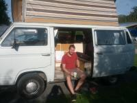 Rick Hurst sitting in the doorway of rocky the vw T25 campervan